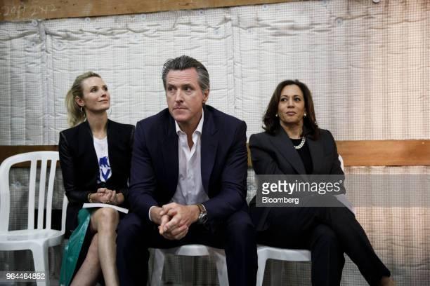 Gavin Newsom Democratic candidate for governor of California center sits next to his wife Jennifer Newsom left and Senator Kamala Harris a Democrat...
