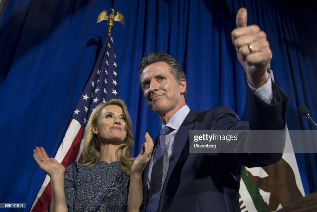 Gavin Newsom, Democratic candidate for governor of California, gives a thumbs-up as his wife Jennifer Siebel Newsom, looks on during a primary election watch party in San Francisco, California, U.S., on Tuesday, June 5, 2018. Lieutenant GovernorNewsomand Republican businessman John Cox won the most votes in Californias gubernatorial primary, advancing to a general election that will test the states position as leader of the resistance to PresidentDonald Trump. Photographer: David Paul Morris/Bloomberg via Getty Images