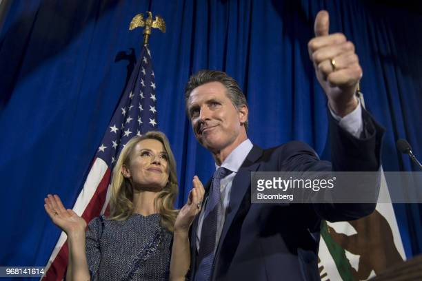 Gavin Newsom Democratic candidate for governor of California gives a thumbsup as his wife Jennifer Siebel Newsom looks on during a primary election...