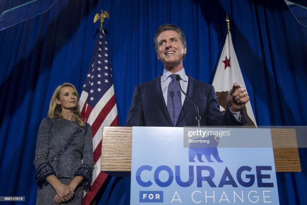 Gavin Newsom, Democratic candidate for governor of California, right, speaks as his wife Jennifer Siebel Newsom listens during a primary election watch party in San Francisco, California, U.S., on Tuesday, June 5, 2018. Lieutenant GovernorNewsomand Republican businessman John Cox won the most votes in Californias gubernatorial primary, advancing to a general election that will test the states position as leader of the resistance to PresidentDonald Trump. Photographer: David Paul Morris/Bloomberg via Getty Images