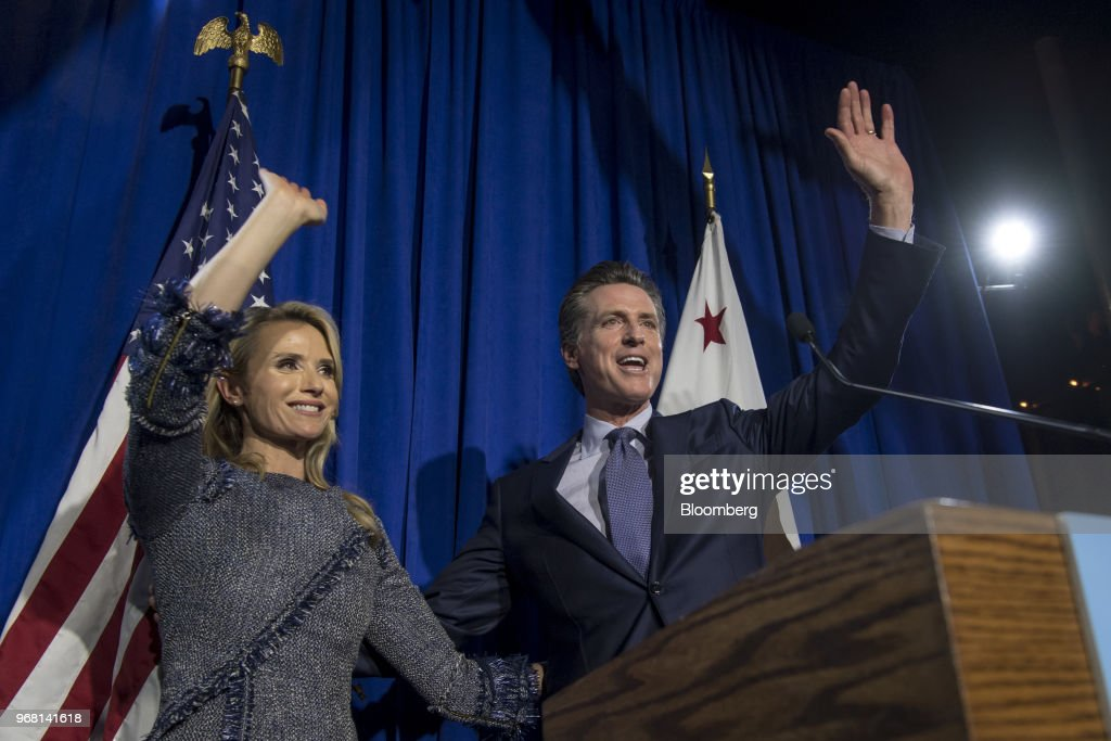 Gavin Newsom, Democratic candidate for governor of California, right, and his wife Jennifer Siebel Newsom, wave to attendees during a primary election watch party in San Francisco, California, U.S., on Tuesday, June 5, 2018. Lieutenant GovernorNewsomand Republican businessman John Cox won the most votes in Californias gubernatorial primary, advancing to a general election that will test the states position as leader of the resistance to PresidentDonald Trump. Photographer: David Paul Morris/Bloomberg via Getty Images