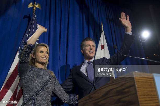 Gavin Newsom Democratic candidate for governor of California right and his wife Jennifer Siebel Newsom wave to attendees during a primary election...