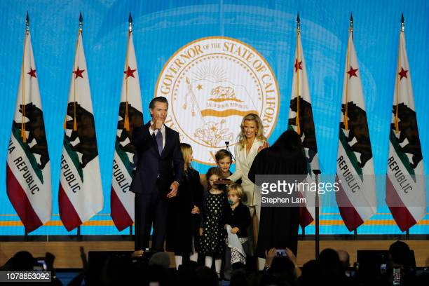 Gavin Newsom gestures to the crowd after being sworn in as governor of California alongside children Montana Brooklynn Hunter Dutch and wife Jennifer...