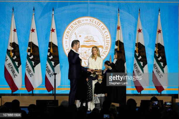 Gavin Newsom is sworn in as governor of California by California Chief Justice Tani Gorre CantilSakauye as Newsom's wife Jennifer Siebel Newsom...