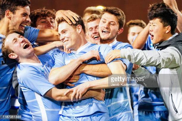 Gavin Tasker of Tufts Jumbos is congratulated by his teammates after being named the offensive player of the tournament during the Division III Men's...