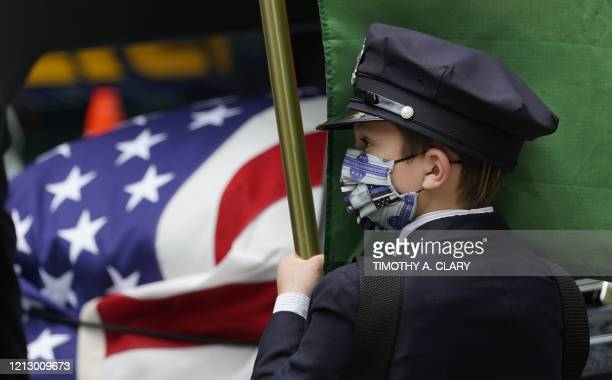 Gavinage 10 the son the late Glen Ridge Police Officer Charles Rob Roberts looks on as pallbearers carry the casket of his father who died of...