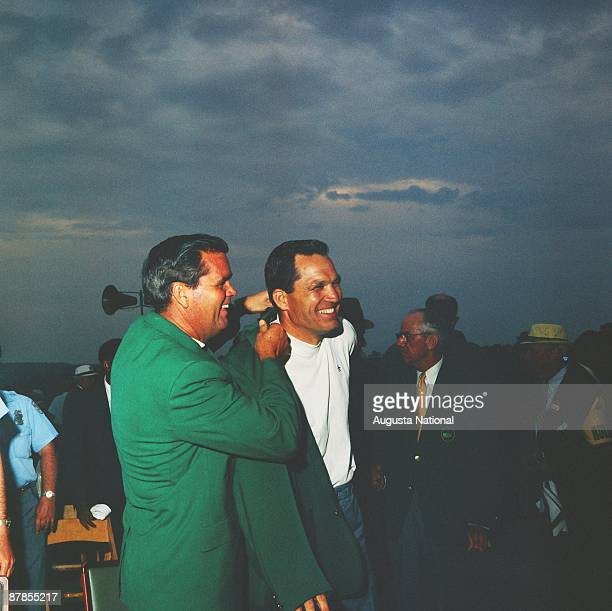 Gay Brewer helps Masters Champion Bob Goalby with his Green Jacket at the Presentation Ceremony during the 1968 Masters Tournament at Augusta...