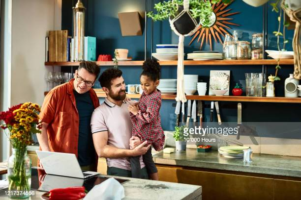 gay couple and daughter doing video call on laptop -  lgbtqi ストックフォトと画像