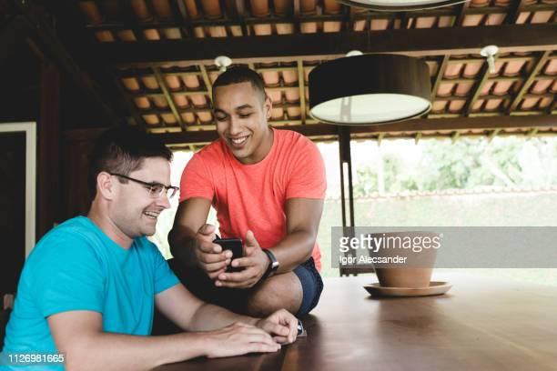 gay couple at backyard - sentar se imagens e fotografias de stock