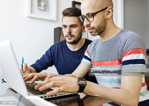 Gay Couple At Home Working On Laptop
