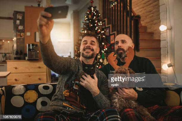 gay couple celebrating christmas - national holiday stock pictures, royalty-free photos & images