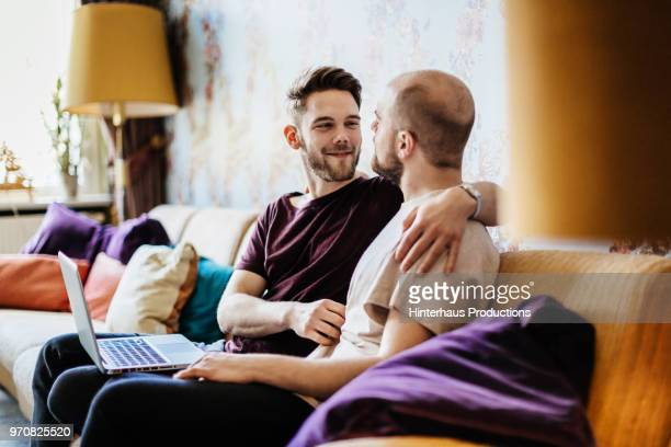 Gay Couple Chatting And Relaxing At Home.