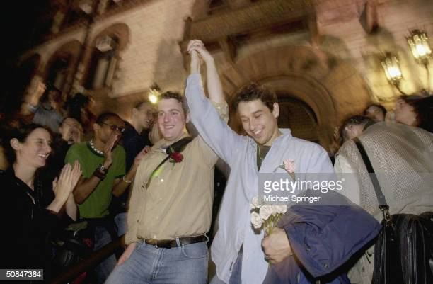 Gay couple clasp hands in response to applause from a large crowd as they emerge from City Hall after applying for a marriage license in the early...