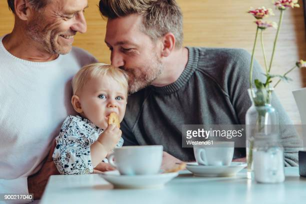 Gay couple cuddling with their baby in cafe