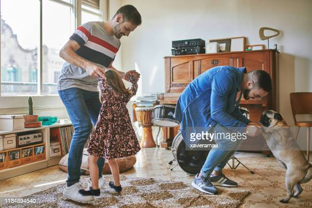 Gay couple dancing with daughter and pug at home