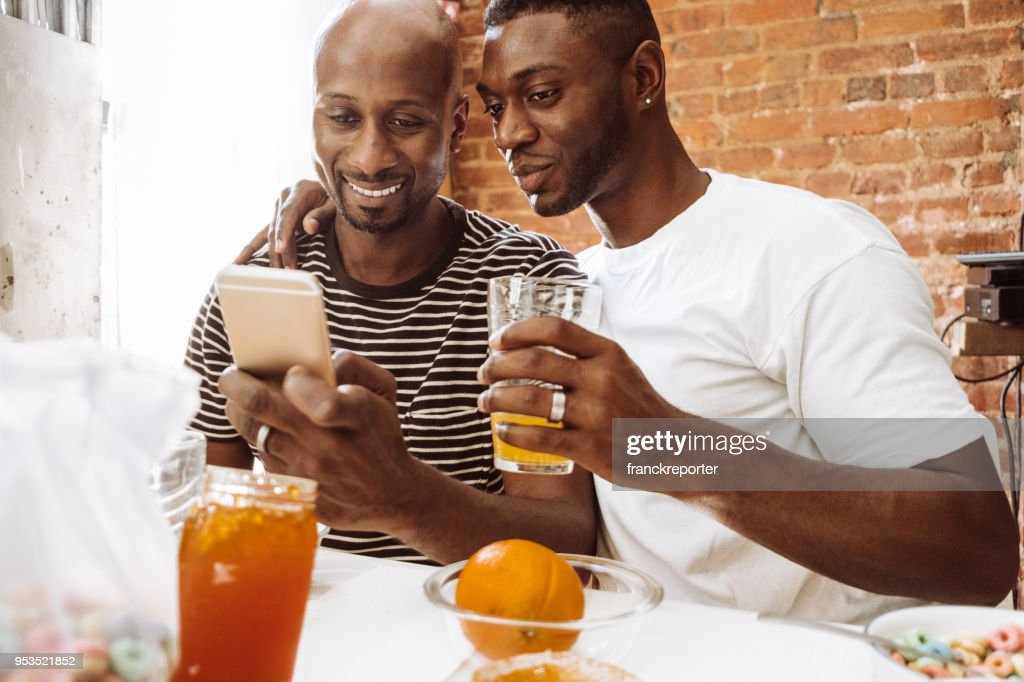 gay couple doing breakfast at home : Stock Photo