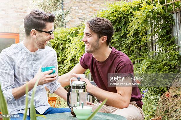 gay couple drinking coffee, chatting in garden.