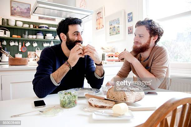 gay couple eating lunch at home - mid volwassen mannen stockfoto's en -beelden