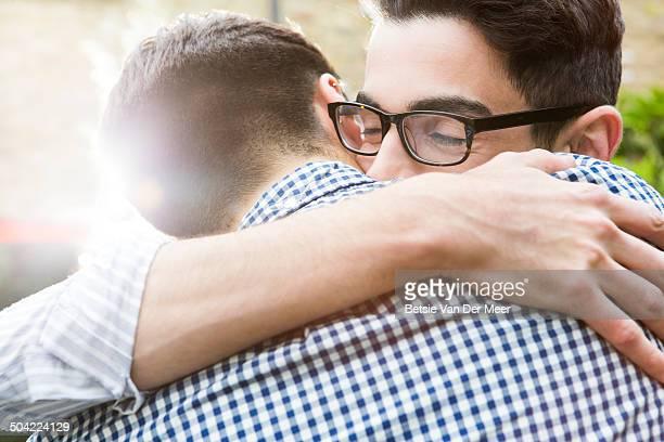 Gay couple embracing, close up.