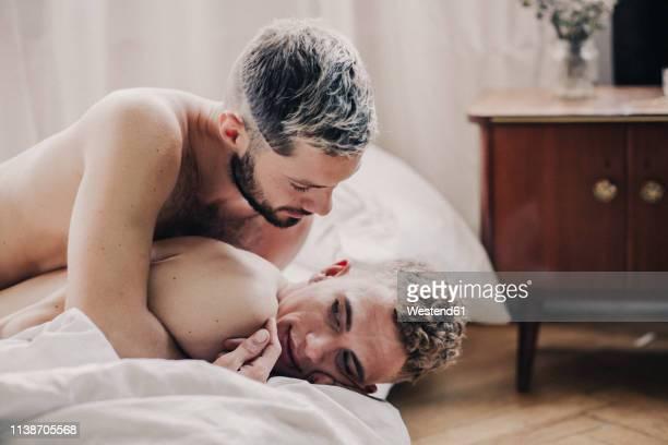 gay couple embracing in bed - erotische umarmung stock-fotos und bilder