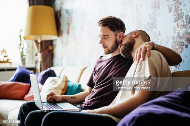 Gay Couple Embracing On Couch Together