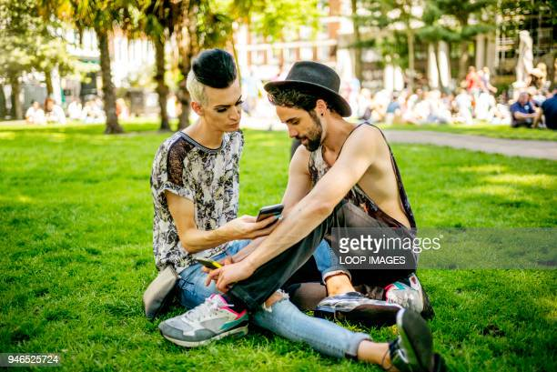 a gay couple enjoy the sunshine as they relax in the park - ロンドン ソーホー ストックフォトと画像