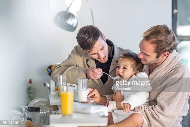 Gay couple feeding son breakfast