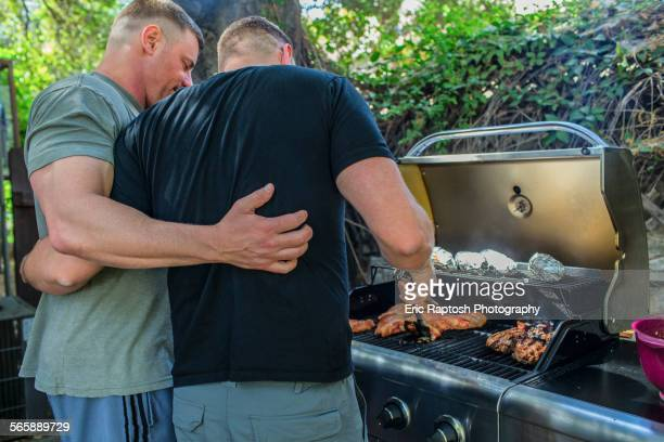 Gay couple grilling food in backyard
