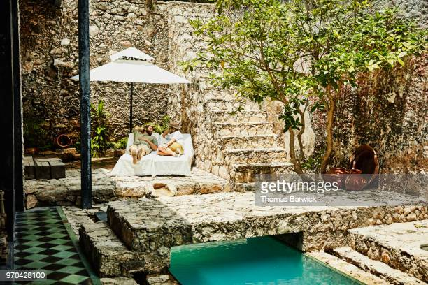 Gay couple hanging out together on lounge chairs by pool in courtyard of boutique hotel