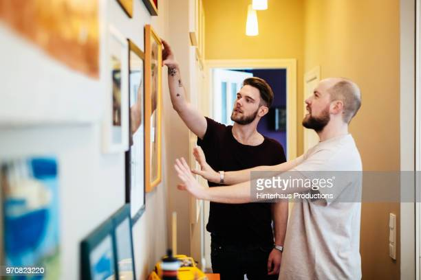 gay couple hanging pictures together - hanging stock pictures, royalty-free photos & images