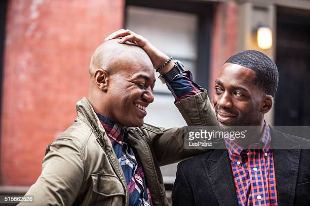 gay couple having fun together in new york city - flirting stock pictures, royalty-free photos & images