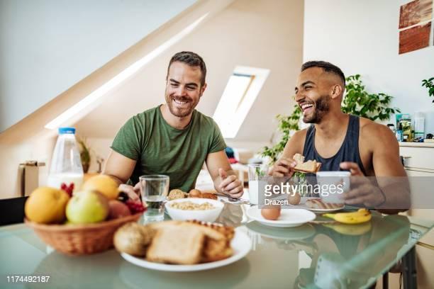couples gais ayant le petit déjeuner sain dans le lit confortable et le petit déjeuner - beautiful gay men photos et images de collection