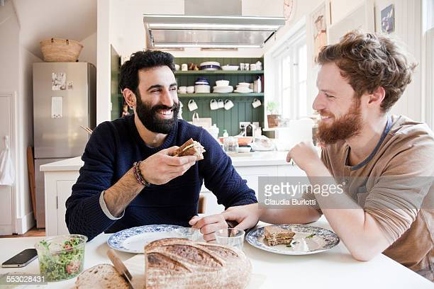 gay couple having lunch at home - lunch stock pictures, royalty-free photos & images