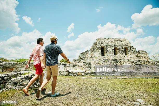 Gay couple holding hands while exploring Mayapan ruins during vacation