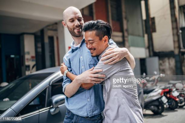 gay couple hugging and walking on the street - east asian ethnicity stock pictures, royalty-free photos & images