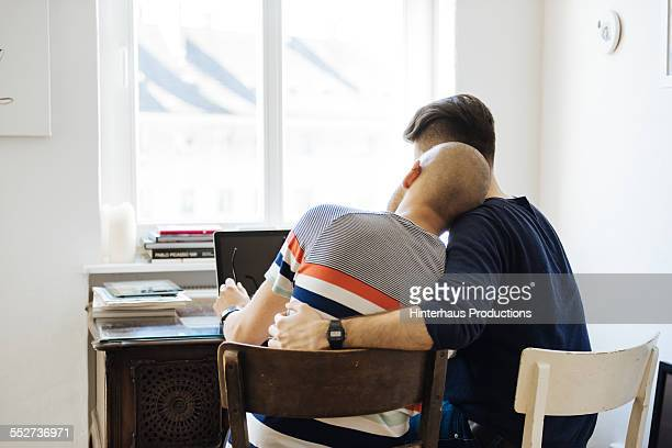 Gay Couple Hugging At Desk