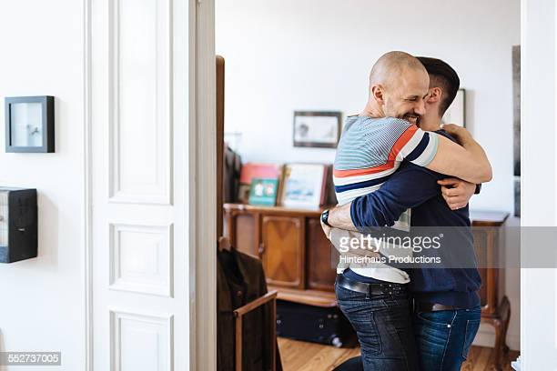 Gay Couple Hugging In Their Apartment