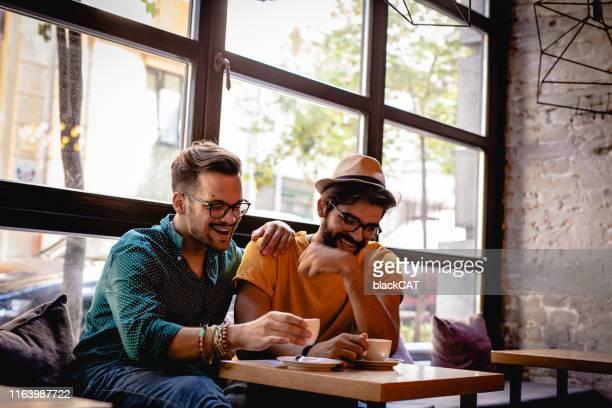 couple gay dans un café. hommes lgbt - beautiful gay men photos et images de collection