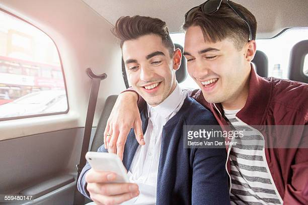 Gay couple in back of cab, looking at phone