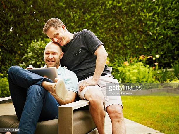 Gay couple in backyard working on digital tablet