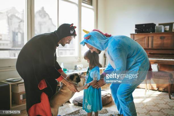 gay couple in costumes dancing with child and pug - mask dance stock pictures, royalty-free photos & images