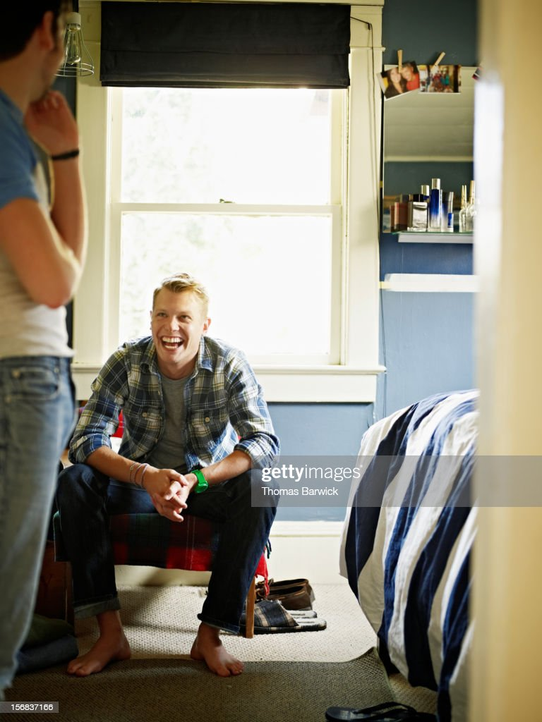 Gay couple in discussion in bedroom laughing : Foto de stock