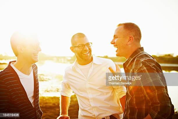 Gay couple in discussion with friend at sunset