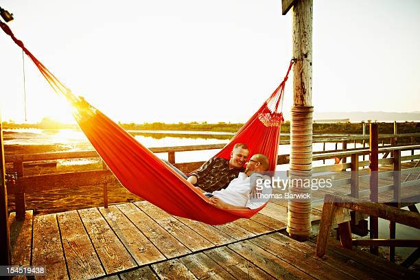 Gay couple in hammock on dock at sunset