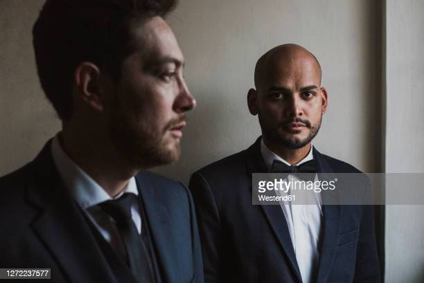 Gay couple in suits standing against wall on wedding day