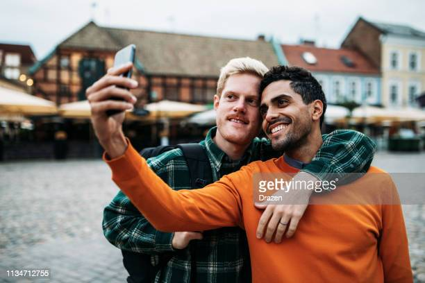 gay couple in sweden - latino and scandinavian gay men enjoying their common life together - malmo stock pictures, royalty-free photos & images