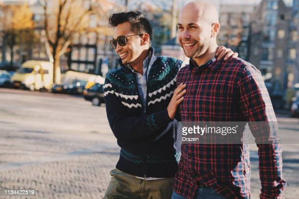 gay couple - indonesian and european guys are in relationship and spending time on city break - eastern european descent stock pictures, royalty-free photos & images