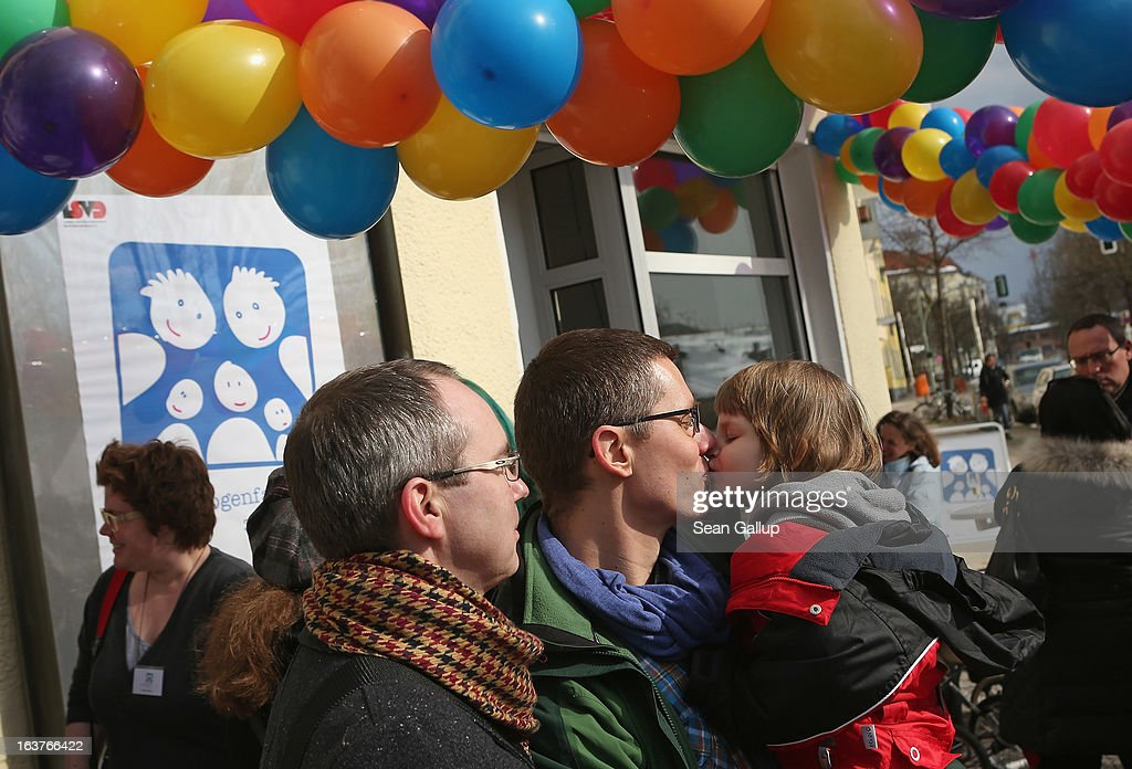 Gay couple Kai (L) and Michael Korok nuzzle with their daughter Jana, 4, at Germany's first gay parent counseling center on its opening day on March 15, 2013 in Berlin, Germany. The Regenbogenfamilien Zentrum (Rainbow Families Center) will provide counseling and other services to families with gay, lesbian and transgender parents. Gay marriage is legal in Germany though gay couples are not entitled to the same full legal rights as heterosexual couples, and the issue of child adoption by gay couples remains legally somewhat complicated.