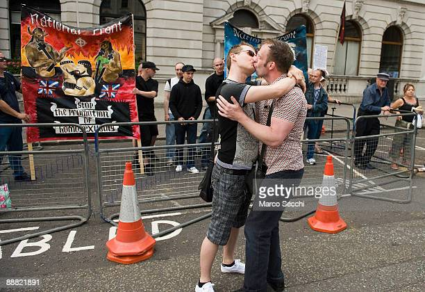 A gay couple kiss in front of a small group of protesters from the National Front during the London Pride Parade on July 4 2009 in London England...