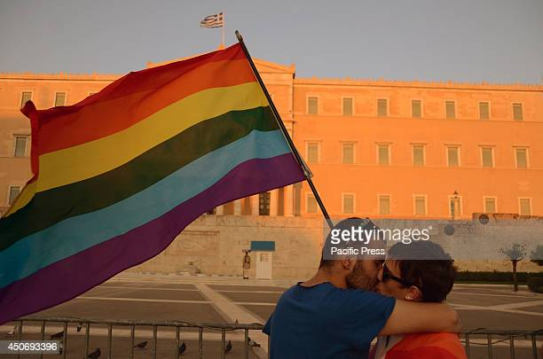 A gay couple kiss in front of the Greek parliament building whilst holding a Rainbow colored flag Hundreds of people on Saturday joined Greece's...